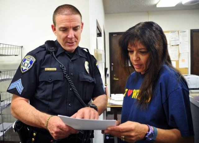 Sgt. Charlie Eipper turns in a report to records supervisor Alice Harrison during his shift as an officer for the Wichita Falls Police Department in Wichita Falls, Texas.  Image Credit: rtv6News