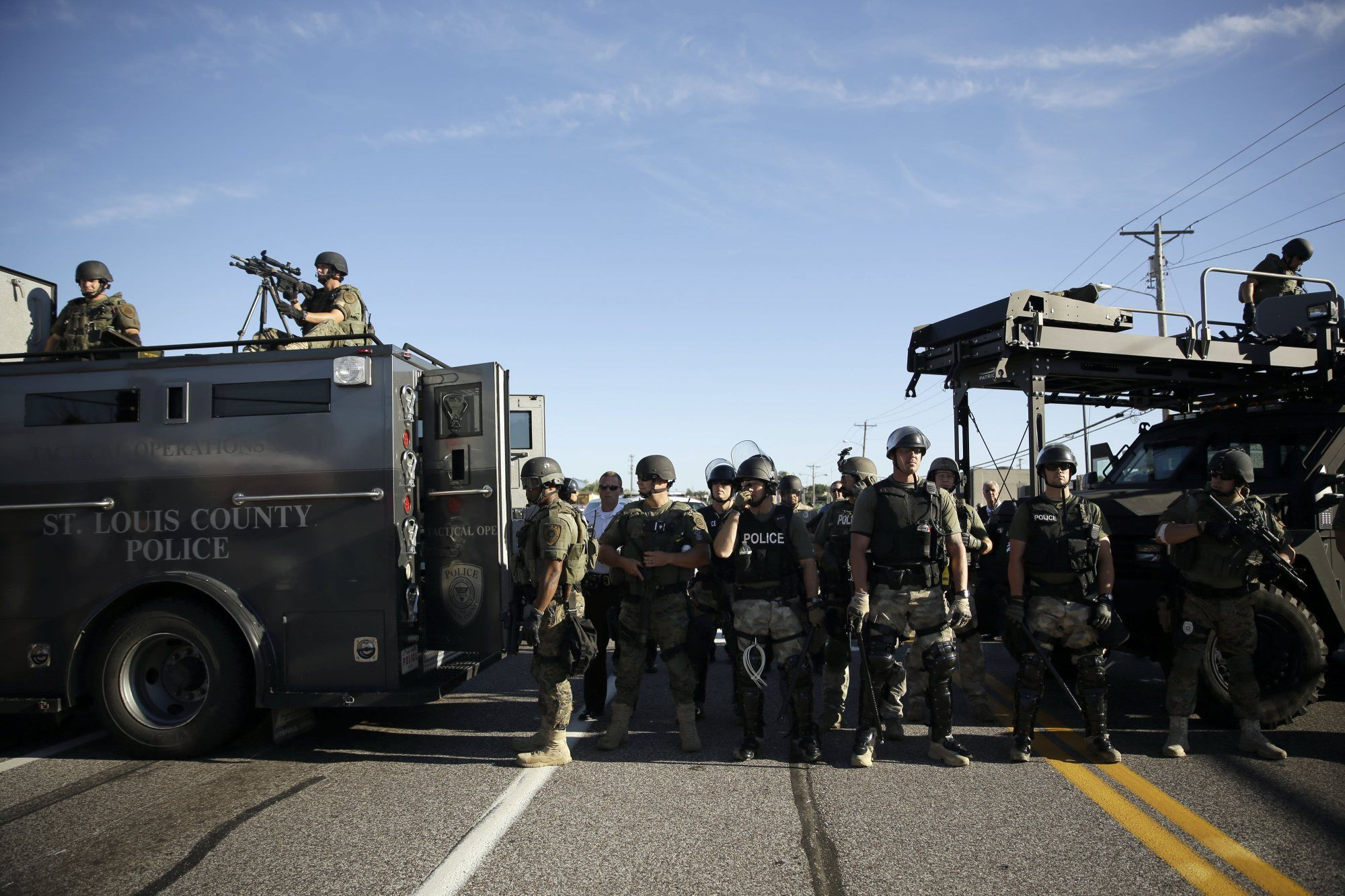 Police in riot gear watch protesters in Ferguson, Mo. on Aug. 13, 2014. Jeff Roberson—AP