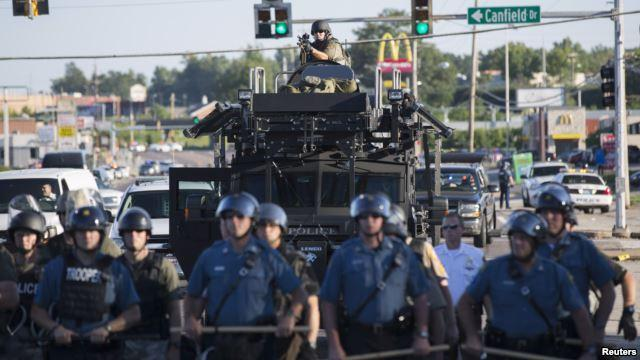 Riot police stand guard as demonstrators protest the shooting death of teenager Michael Brown in Ferguson, Missour: Reuters